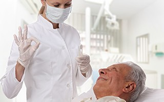Older man in dental chair smiling at dentist