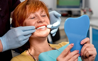 Woman and dentist looking at smile in mirror