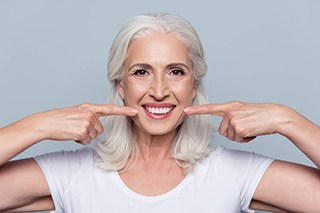Older woman pointing to flawless smile