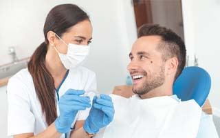 Young woman with Invisalign Clear Braces smiling in dental chair