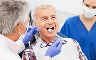 Man in dental chair receiving dentistry exam