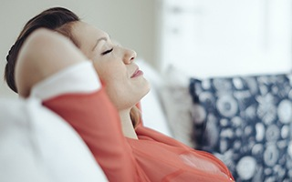 Woman relaxing on couch with hands behind head