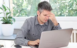 Man holding his head while working on laptop
